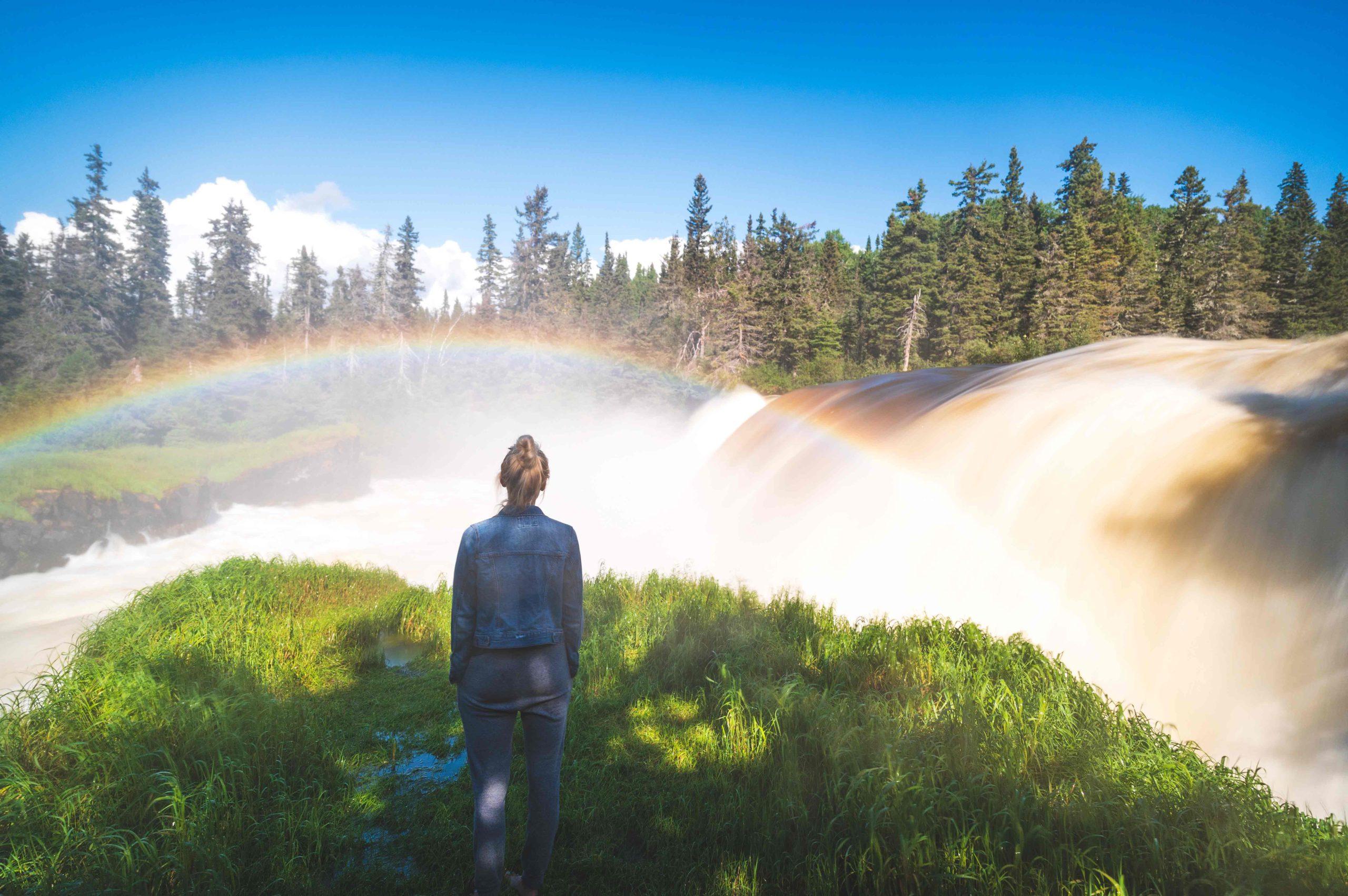 Avery Kash looking at waterfall and rainbow.
